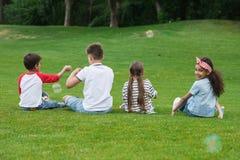 Enfants multi-ethniques mignons jouant avec des bulles de savon tout en se reposant sur l'herbe verte en parc Photo stock
