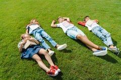 Enfants multi-ethniques mignons se trouvant sur le pré vert avec des livres Image stock