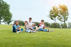 Enfants multi-ethniques soufflant des bulles de savon tout en se reposant ensemble en parc Images libres de droits