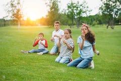Enfants multi-ethniques soufflant des bulles de savon tout en se reposant sur la pelouse verte en parc Image libre de droits