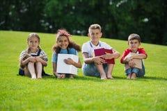 Enfants multi-ethniques tenant des livres tout en se reposant sur l'herbe verte et souriant à l'appareil-photo Photo stock