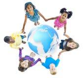 Enfants multi-ethniques tenant des mains autour du globe Photographie stock