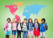 Enfants multiculturels d'école devant la carte colorée du monde Images libres de droits