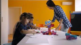 Enfants multiculturels dessinant dans le jardin d'enfants banque de vidéos