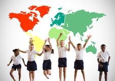 Enfants multiculturels sautant devant la carte colorée du monde Photos stock