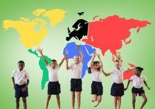 Enfants multiculturels sautant devant la carte colorée du monde Images stock