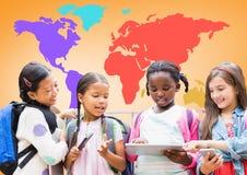 Enfants multiculturels sur des dispositifs devant la carte colorée du monde Photographie stock libre de droits