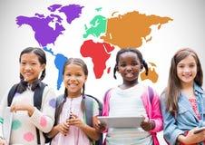 Enfants multiculturels sur des dispositifs devant la carte colorée du monde Photo stock