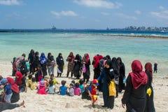 Enfants musulmans jouant à la plage ainsi que leurs parents photos libres de droits