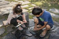Enfants nettoyant des ustensiles dehors photo libre de droits