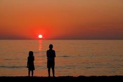 Enfants observant le coucher du soleil Photographie stock
