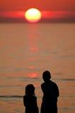Enfants observant le coucher du soleil Image libre de droits