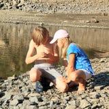 Enfants observant une coquille par un lac Photographie stock