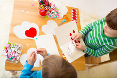 Enfants occupés dans des arts de Saint-Valentin avec des coeurs Photographie stock