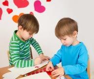 Enfants occupés dans des arts de Saint-Valentin avec des coeurs Photos stock