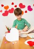 Enfants occupés dans des arts de Saint-Valentin avec des coeurs Images stock