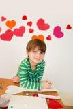 Enfants occupés dans des arts de Saint-Valentin avec des coeurs Photo libre de droits