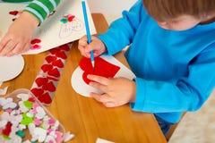 Enfants occupés dans des arts de Saint-Valentin avec des coeurs Image libre de droits