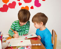 Enfants occupés dans des arts de Saint-Valentin avec des coeurs Photographie stock libre de droits