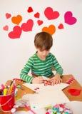 Enfants occupés dans des arts de Saint-Valentin avec des coeurs Photos libres de droits