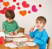 Enfants occupés dans des arts de Saint-Valentin avec des coeurs Images libres de droits