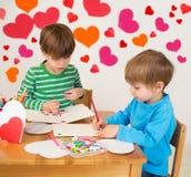 Enfants occupés dans des arts de Saint-Valentin avec des coeurs Photo stock