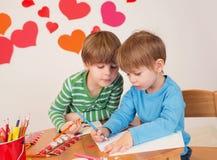 Enfants occupés dans des arts de Saint-Valentin avec des coeurs Image stock