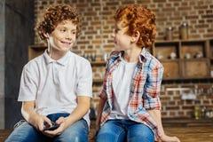 Enfants occupés positifs bavardant dans la cuisine Photos stock