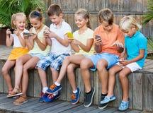 Enfants occupés tenant des smartphones et se reposer Image libre de droits