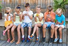 Enfants occupés tenant des smartphones et se reposer Photographie stock libre de droits