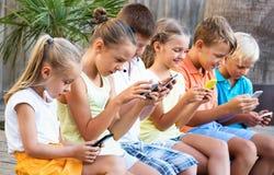 Enfants occupés tenant des smartphones et se reposer Photos libres de droits