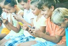 Enfants occupés tenant des smartphones et se reposer Images libres de droits