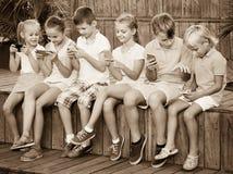 Enfants occupés tenant des smartphones et se reposer Image stock