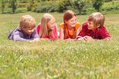 Enfants optimistes se trouvant sur l'herbe dans cru Photos stock
