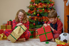 Enfants ouvrant des cadeaux de Noël Photos stock
