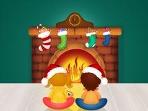 Enfants par la cheminée le réveillon de Noël Images libres de droits