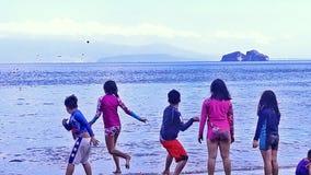 Enfants par la plage au jeu Images stock