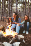 Enfants par le feu dans la forêt d'automne Photographie stock