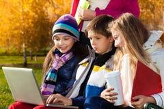 Enfants parlant avec l'ordinateur portable dehors Images libres de droits