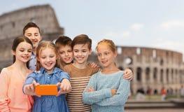 Enfants parlant le selfie de smartphone au-dessus du Colisé Photographie stock libre de droits