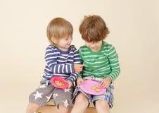 Enfants partageant un casse-croûte, nourriture, la mode des enfants Photographie stock libre de droits