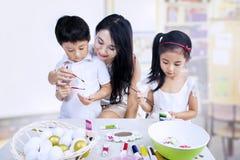 Enfants peignant des oeufs dans la classe Photos stock