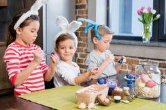 Enfants peignant des oeufs de pâques Photos stock