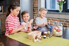 Enfants peignant des oeufs de pâques Photographie stock