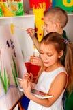Enfants peignant le doigt sur le chevalet Groupe seuls d'enfants à l'école de classe image libre de droits