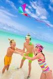Enfants pilotant le cerf-volant en mer Images stock