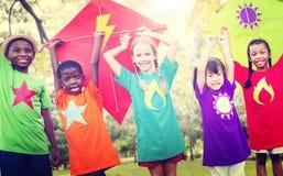 Enfants pilotant le concept espiègle d'amitié de cerf-volant Photographie stock libre de droits