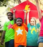 Enfants pilotant le concept espiègle d'amitié de cerf-volant Photo stock