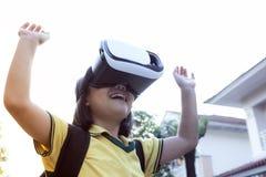 Enfants portant des lunettes de réalité virtuelle avec l'amusement et la position étonnante de visage extérieurs photographie stock libre de droits