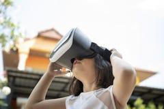 Enfants portant des lunettes de réalité virtuelle avec l'amusement et la position étonnante de visage extérieurs photos stock